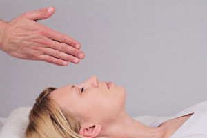Attractive young woman having reiki healing treatment , alternative medicine concept.