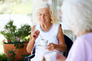Visiting old mature woman having tea and laughing